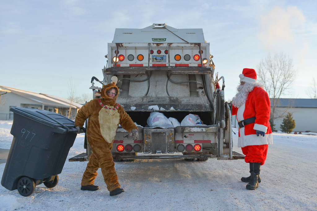 Justin Sheely | The Sheridan Press<br /> Town of Ranchester employees Jill LaToush, left, and Robert Miller, as Santa Claus, empty garbage bins in December in Ranchester. Waste Management staff wore festive costumes while collecting garbage bins around town.