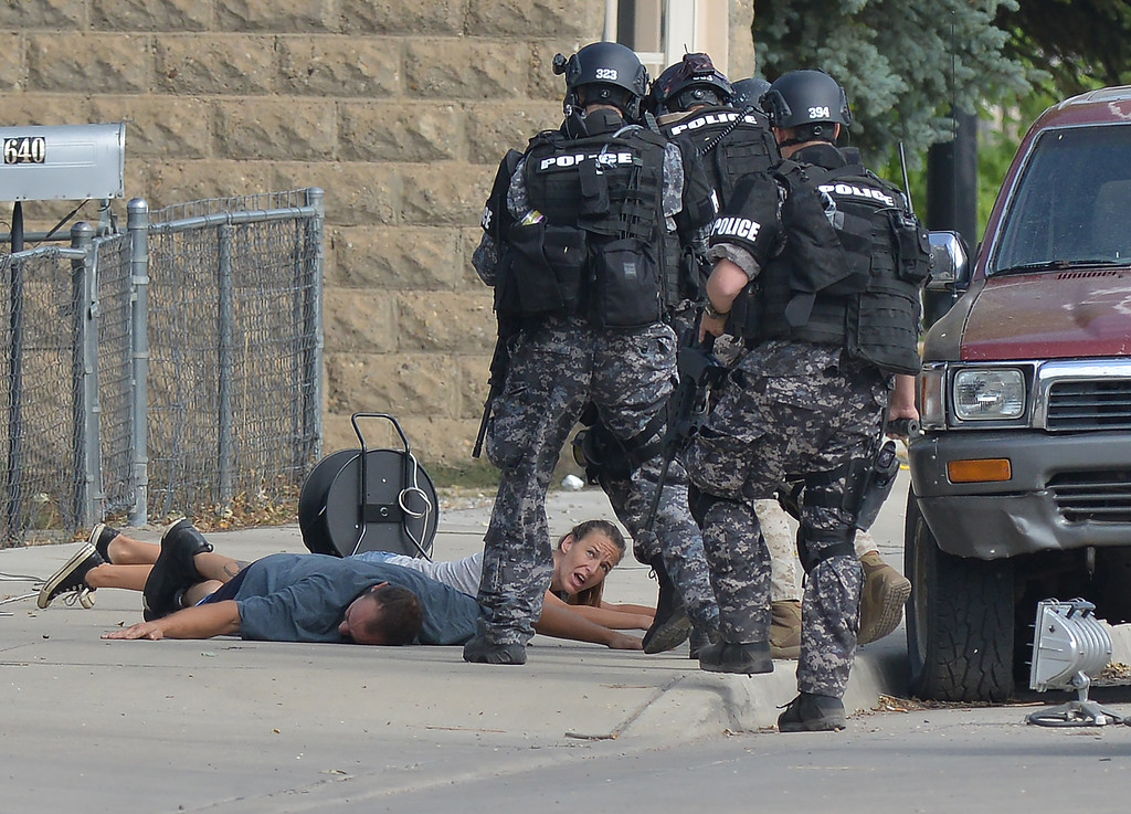 Justin Sheely | The Sheridan Press<br /> Scott Bronson, left, and Michelle Lakey put their hands up and get on the ground as law enforcement surrounds them on Saturday, Sept. 3, 2016. Bronson was armed and had barricaded himself with Lankey inside a home at 632 Broadway St. since Wednesday evening.
