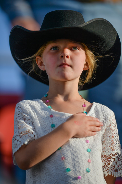 Justin Sheely | The Sheridan Press<br /> Five-year-old Tinley Barnes holds her hand above her heart for the national anthem during the first night of the Sheridan WYO Rodeo last July at the Sheridan County Fairgrounds.
