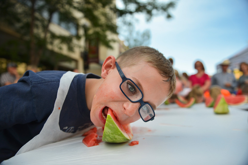 Justin Sheely | The Sheridan Press<br /> Seven-year-old Brandon Graham digs into his slice for a watermelon eating contest during the Third Thursday street festival on Main Street.