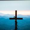 christian worship cross overlooking mountains at sunrise
