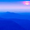 sunrise sun peeks through the clouds over mountain range