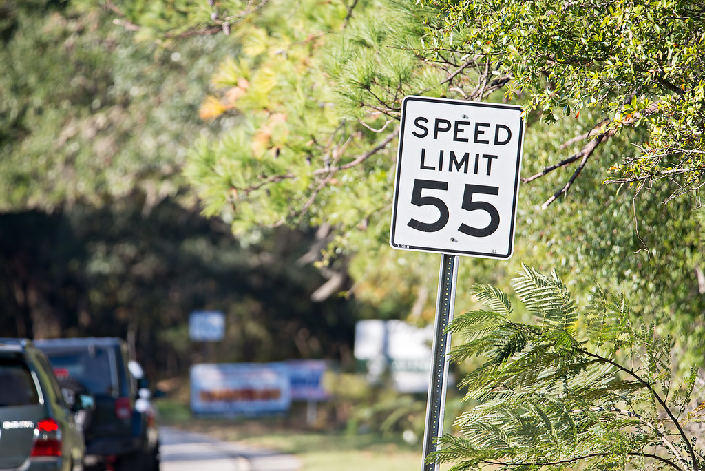"White sign with ""speed limit 55"" printed in black on country road"