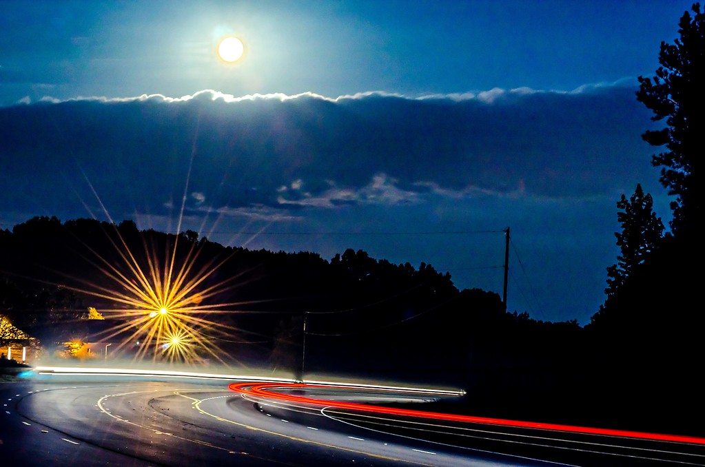 harvest moon glowing over busy highway traffic