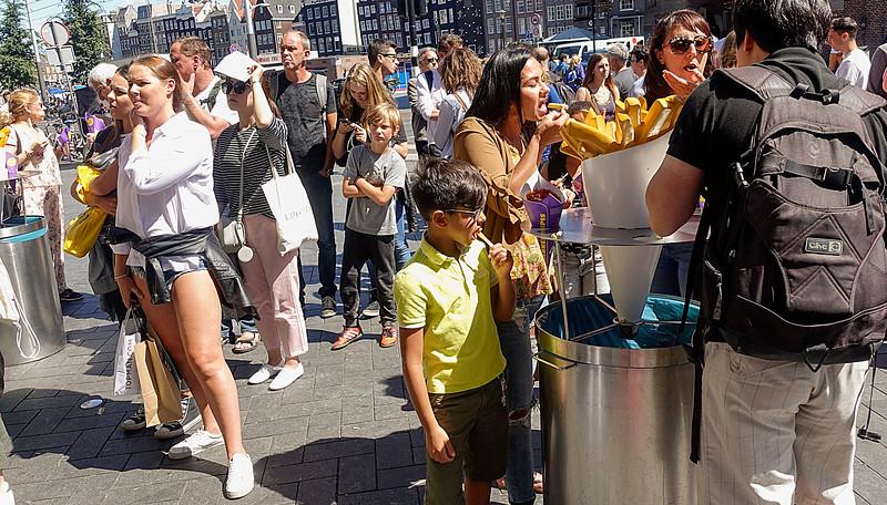 Nederland, Amsterdam, Centrum, friet eten Damrak, 1 augustus 2016, foto: Katrien Mulder