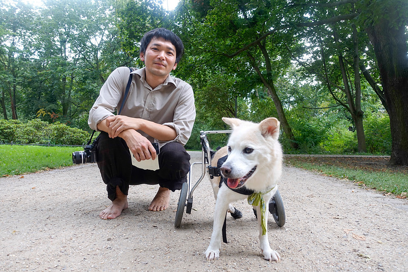 Germany, Berlin, 28 augustus 2016, Takao Hashimoto is een japanse fotograaf. Vijf jaar geleden kwam hij naar Duitsland met zijn hondje Kuh dat nu 12 jaar is. Kuhs achterpoten zijn verlamd sinds zijn vroegste jeugd. Hij sleept zich onafhankelijk voort met behulp van zijn voorpoten en een ingenieus karretje. Takao fotografeert met een analoge nikon spiegelreflex camera. Takao Hashimoto is a Japanese photographer. Five years ago he came to Germany with his Doggie Kuh that is now 12 years old. Kuhs hind legs are paralyzed since his earliest youth. He drags independent on using his front legs and an ingenious trolley. Takao photographs with an analog nikon SLR camera. foto: Katrien Mulder