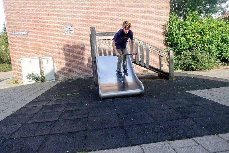Nederland, Amsterdam, Amsterdam Oost, Jongen  rijdt met step van glijbaantje;  Boy rides with scooter from slide;  3 september 2016, foto: Katrien Mulder