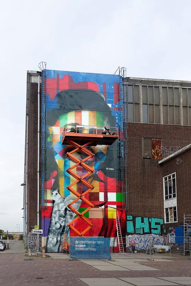 Nederland, Amsterdam, Amsterdam Noord, NDSM Terrein, wereldberoende Braziliaanse streetartist Eduardo Kobra realiseert deze week een monumentaal portret van Anne Frank op de noordelijke buitenmuur van de loods op de hoek van de MS van Riemsdijkweg,  en de Tt Neveritaweg, famous Brazilian street artist Eduardo Kobra   realizes this week a monumental portrait of Anne Frank, de man rechts in de hoogwerker is Eduardo Kobra, the man at the right side of the platform is Eduardo Kobra, 26 september 2016, foto: Katrien Mulder