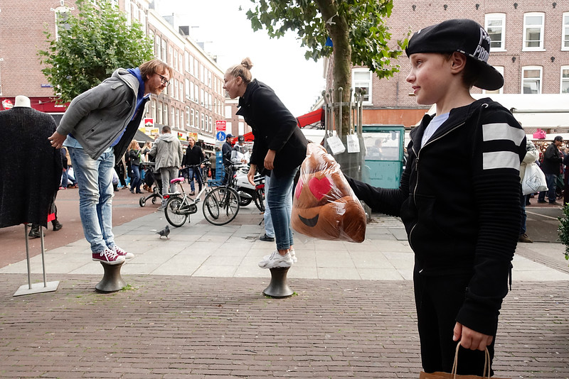 Nederland, Amsterdam, Albert Cuypmarkt, een gezin is aan het winkelen en ondertussen aeen soort handenklap spel aan het doen, 8 oktober 2016, foto: Katrien Mulder