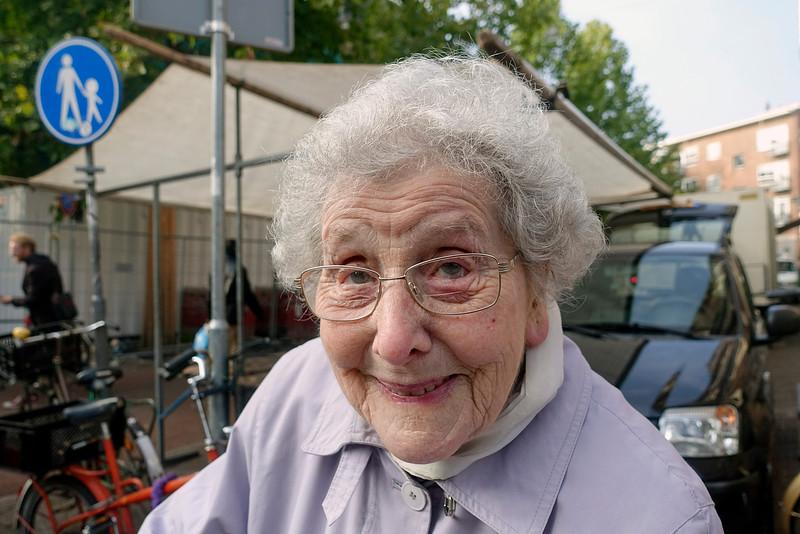 Nederland, Amsterdam, Amsterdam Zuid, de Pijp, 26 oktober 2016, Anneke, 98 jaar, heeft op de markt een lamp gezien voor 5 euro die ze even daarvoor in een winkel gekocht had voor 35 euro. Ze kan em alleen ruilen voor een tegoedbon, maar in die winkel hebben ze niks wat ze nodig heeft, dus ze laat het maar zo. Ze ziet er goed uit voor zo'n hoge leeftijd, dat komt omdat ze alleen water en zeep heeft gebruikt voor haar gezicht. Anneke, 98 years, has seen on the market  a lamp for 5 euros only, which she had bought in a store moments before for 35 euros. She can only exchange it for a voucher, but they have nothing   in the store she needs, so forget it . She looks pretty good for such an old age, that's because she used only soap and water to her face.foto: Katrien mulder