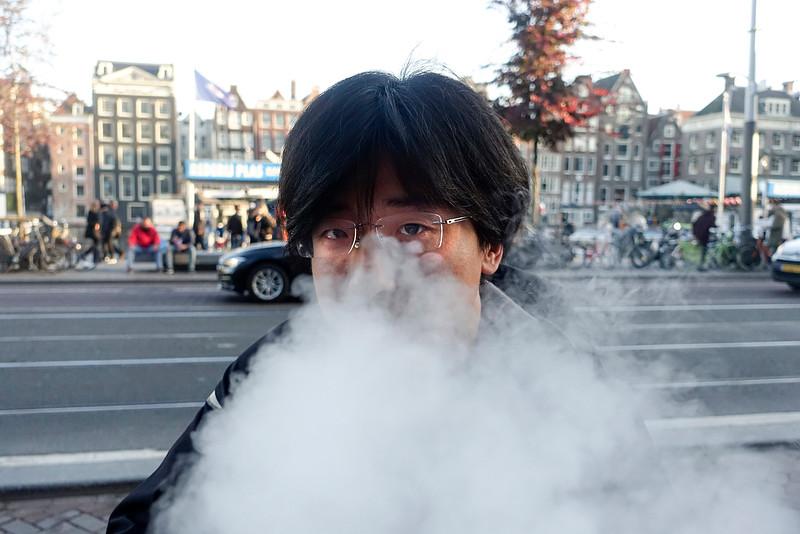 Nederland, Amsterdam, Damrak, de heer Wang rookt  een Kangertech sigaret, een soort draagbare , hij legt uit dat het een soort draagbare shisha is, 31 oktober 2016, foto: Katrien Mulder