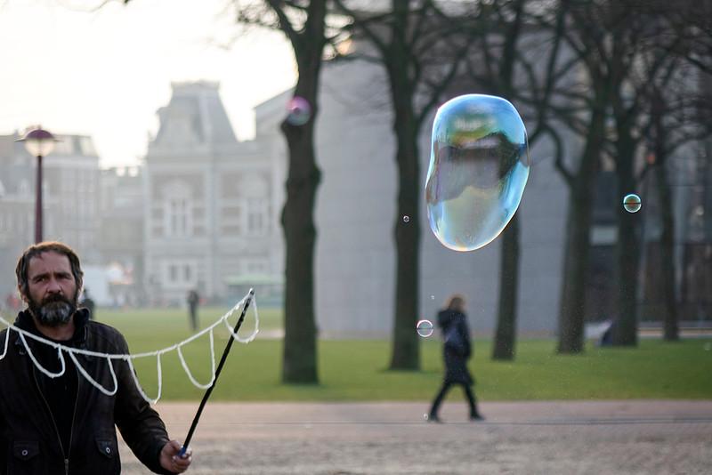 Nederland, Amsterdam, Museunplein; man blaast grote bellen; foto: Katrien Mulder