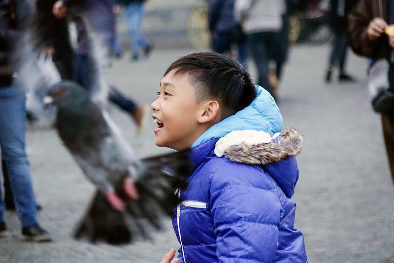 Nederland, Amsterdam, de Dam, Aziatische jongen rent tussen de duiven  14 december 2016, foto: Katrien Mulder