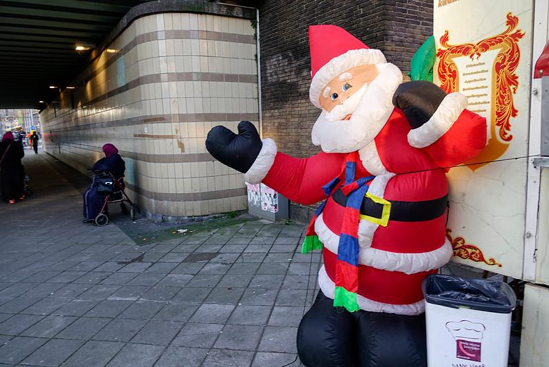 Nederland, Amsterdam, Amsterdam Oost, In de Javastraat, bij het viaduct onder de spoorlijn staat een oliebollenkraam, aan de  de ene kant geflankeerd door  een plastic opblaas-kerstboom en dito opblaas-sneeuwpop, en aan de andere kant door een opblaas-kerstman. De laatste  zakt langzaam inelkaar omdat iemand er een gaatje in geprikt heeft. De eigenaar van de oliebollenkraam heeft deze opblaasbare kerstversiering twaalf jaar geleden op de kop getikt. 16 december 2016, foto: Katrien Mulder