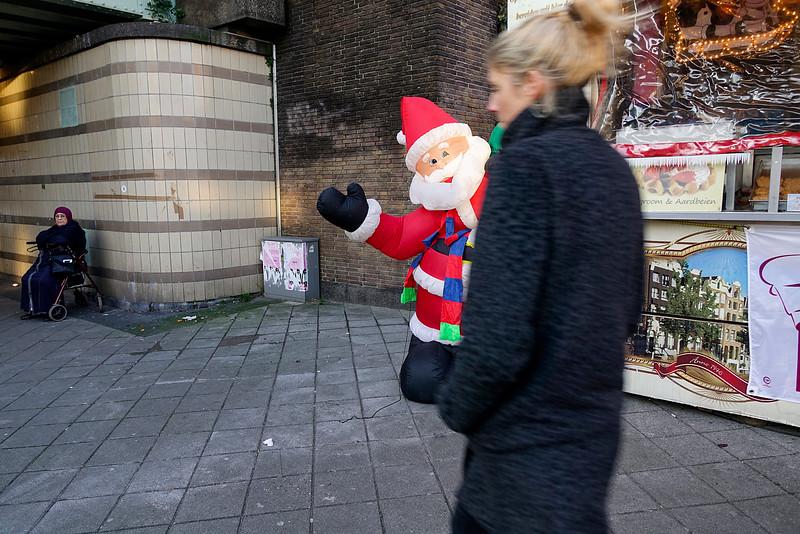 Nederland, Amsterdam, Amsterdam Oost, In de Javastraat, bij het viaduct onder de spoorlijn staat een oliebollenkraam, aan  de ene kant geflankeerd door  een plastic opblaas-kerstboom en dito opblaas-sneeuwpop, en aan de andere kant door een opblaas-kerstman. De laatste  zakt langzaam inelkaar omdat iemand er een gaatje in geprikt heeft. De eigenaar van de oliebollenkraam heeft deze opblaasbare kerstversiering twaalf jaar geleden op de kop getikt. 16 december 2016, foto: Katrien Mulder
