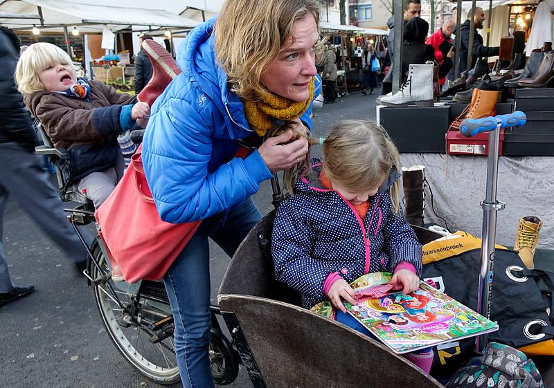 Nederland, Amsterdam, Amsterdam Oost, Pien leest heel veel, nu leest ze een prisessenboek van Walt Disney, haar lievelingsboek is een ander prinsessenboek van Walt Disney, haar broertje Teun  probeert zijn laars aan te trekken;16 december 2016, foto: Katrien Mulder