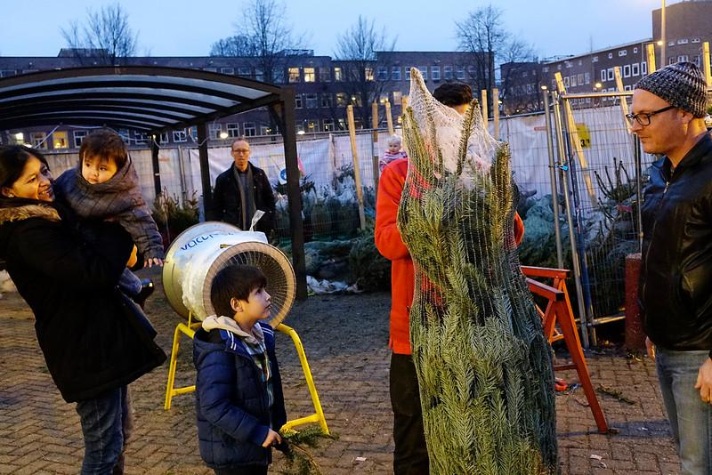 Nederland, Amsterdam, Amsterdam Oost,  na lang aarzelen koopt deze famillie een grotere karstboom dan gepland, en nu zijn ze een beetje bang dat de boom verdrietig is omdat zr hem eerst niet wilden. 18 december 2016, foto: Katrien Mulder
