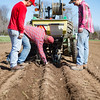 JOED VIERA/STAFF PHOTOGRAPHER- Cambria, NY- Will Hall, Jeff Hall and Dylan Wolfe inspect the soil behind a tractor planting corn at Coulter Farms.