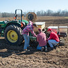 JOED VIERA/STAFF PHOTOGRAPHER- Cambria, NY- Dylan Wolfe, left, helps Jeff and Will Hall adjust their tractor while planting corn on Coulter Farms