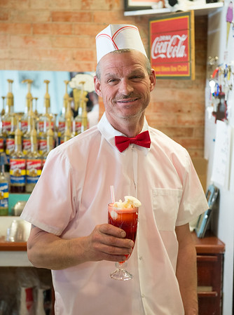 JOED VIERA/STAFF PHOTOGRAPHER-Medina, NY- Jim Blackburn, owner of Meggie Moo's holds up a cherry soda float at the ice cream parlor.