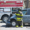 JOED VIERA/STAFF PHOTOGRAPHER- Lockport, NY-A Lockport City Firefighter breaks a window on a minivan at the scene of a two vehicle head on collision on Market Street.
