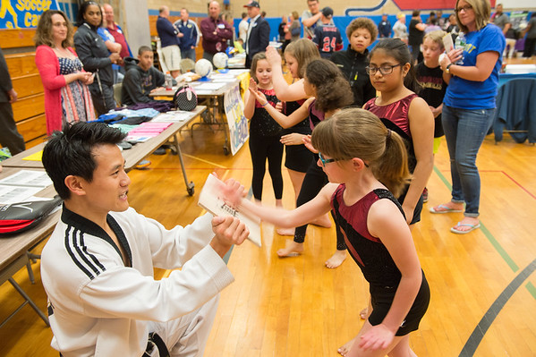 JOED VIERA/STAFF PHOTOGRAPH-Andrew Chong from Master Chong's Tae Kwon Do holds a board while  Mia Clare 9 breaks it during a demonstration at North Park Reading Night.