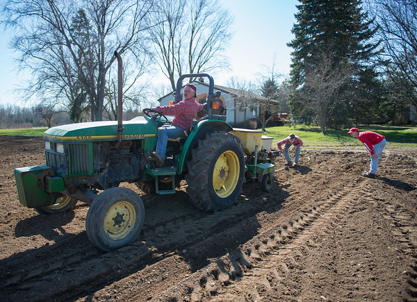 JOED VIERA/STAFF PHOTOGRAPHER- Cambria, NY- Jeff Hall plants corn on a tractor as Dylan Wolfeand his son Will Hall inspect the soil at Coulter Farms