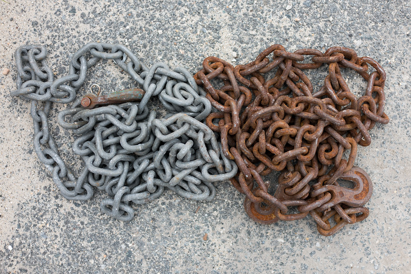 Old Rusty Chain Next to New Clean Chain