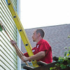 JOED VIERA/STAFF PHOTOGRAPHER-Lockport, NY- Zachary Delaney from Puroclean cleans the side of a fire tainted Webb Street Home.