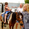 JOED VIERA/STAFF PHOTOGRAPHER-Lockport, NY-Leigh Lindahl from Spirits Wind Farm in Sanborn, NY laughs as Liam Henderson, 5, from Newfane rides a pony guided by 12 year old Kaitlyn Smith.