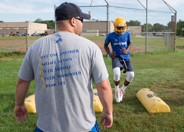 JOED VIERA/STAFF PHOTOGRAPHER-Lockport, NY- Coach Greg Wilson watches as players drill during Lockport High School's first football practice of the season.