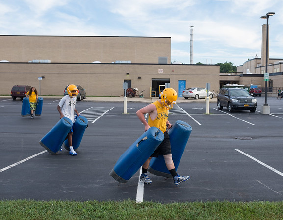 JOED VIERA/STAFF PHOTOGRAPHER-Lockport, NY- players carry pads to Lockport High School's first football practice of the season.