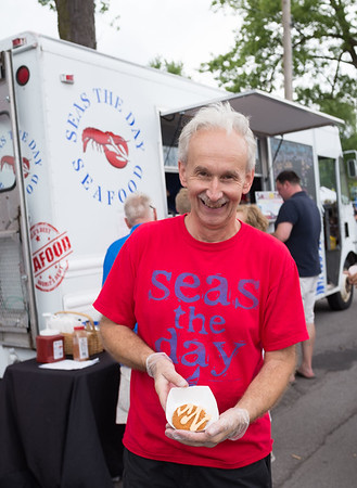 Gene Borowicz holds up Seas the Day's crab cake. The truck won Taste of Lockport's people choice award.