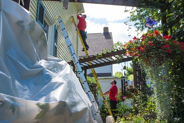 JOED VIERA/STAFF PHOTOGRAPHER-Lockport, NY- Zachary Delaney and Rick Sawyer from Puroclean clean the side of a fire tainted Webb Street Home.