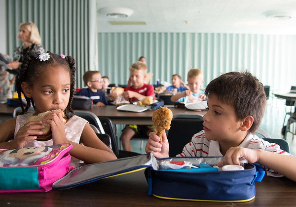 JOED VIERA/STAFF PHOTOGRAPHER-Lockport, NY- Annabel Orona, 7, eats her sandwich as she checks out Giancarlo Pari's, 7 LUnch at the YMCA.
