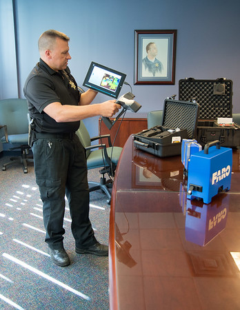JOED VIERA/STAFF PHOTOGRAPHER- Lockport, NY- Niagara County Sheriffs' deptuty crime scene investigator Anthony Giamberdino demonstrates the 3d scanner.
