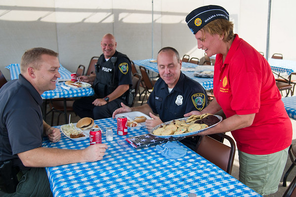 JOED VIERA/STAFF PHOTOGRAPHER-Lockport, NY- American Legion Post 410's Christine Simon serves lunch to Lockport Police Captain Todd Chenez along with Officers Rick Provenzano and Paul Zapp.