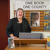 JOED VIERA/STAFF Lockport, NY- Lockport Library director Beverly Federspiel stands behind the display for this year's One Book One County series.