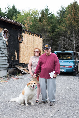 JOED VIERA/STAFF PHOTOGRAPHER- Judy and Zenon Kowal along with their dog Bandit stand by the remains of their Badger Street home.