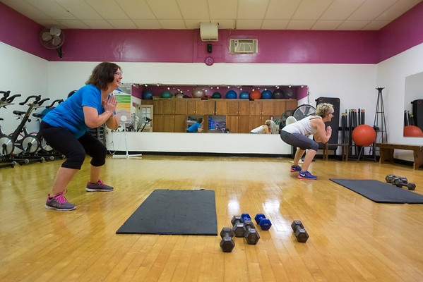 JOED VIERA/STAFF PHOTOGRAPHER-Lockport, NY- Sue Bochenski squats with  Rosalyn Tondera during Core class at the YMCA