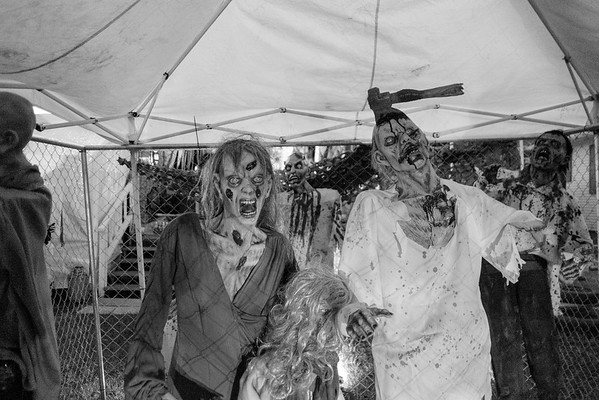 JOED VIERA/STAFF PHOTOGRAPHER-Lockport, NY-Zombies loom under a tent behind a fence at the  halloween display in front of 25 Crosby Avenue.