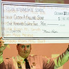 JOED VIERA/STAFF PHOTOGRAPHER-Lockport, NY- Niagara County Sheriff James Voutour holds up a donation check given to him by Regan Intermediate School students.