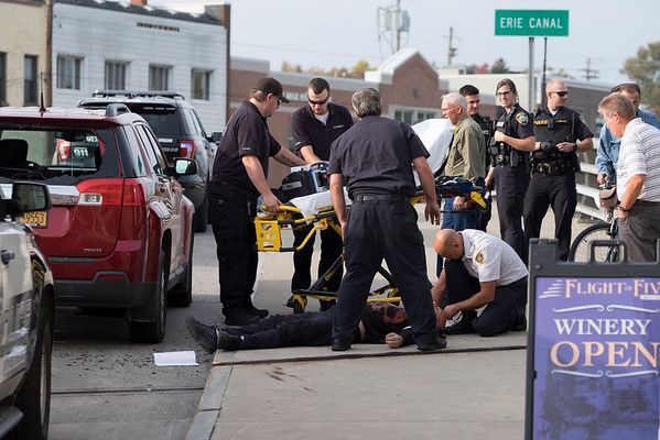 JOED VIERA/STAFF PHOTOGRAPHER-Lockport, NY-First Responders attend to a man who crashed his bike through a vehicles rear windshield.