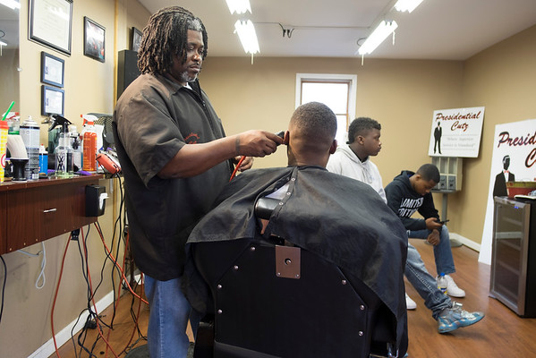 JOED VIERA/STAFF PHOTOGRAPHER-Lockport, NY-Antonio Basser gives Shariff Smith a haircut at Presidential Cutz on Friday afternoon.