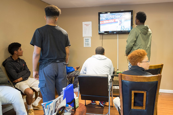 JOED VIERA/STAFF PHOTOGRAPHER-Lockport, NY-A group of young men play Xbox as they wait for a seat on Antonio Basser's barber chair at Presidential Cutz on Friday afternoon.