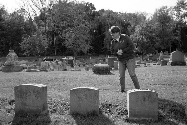 JOED VIERA/STAFF PHOTOGRAPHER-Lockport, NY-Shelley Richards over the grave stones of some of the Sisters of St. Mary at St. Patricks Cemetary are laid across a desk as its designed.