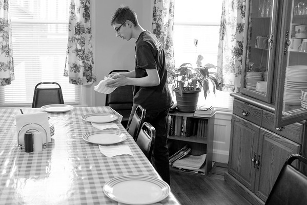 JOED VIERA/STAFF PHOTOGRAPHER-Lockport, NY- Eddie Reeb sets the table for residents at Lockport CARES shelter. Eddie has been volunteering at the shelter with his family since August of 2010.
