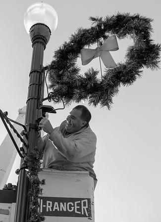 JOED VIERA/STAFF PHOTOGRAPHER-Lockport, NY- Randy Szymanski decorates a light fixture with a wreath up on Main Street.