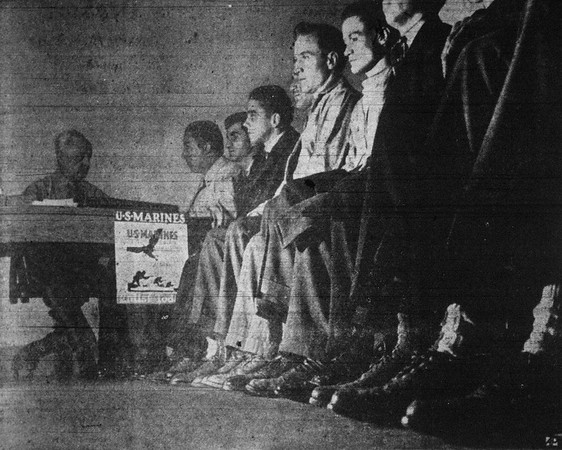 """A photo featured in the December, 22, 1941 edition of the Union-Sun and Journal captioned  """"Feet that soon may be marching to the tune of """"Semper Fidelis"""" await their turn at U.S. marine recruiting station in New York, where enlisment applications have swamped officers."""""""