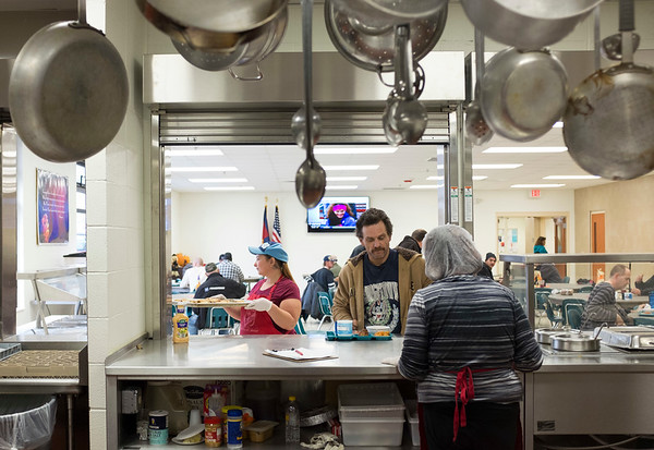 JOED VIERA/STAFF PHOTOGRAPHER-Lockport, NY- Pots and pans hang overhead as lunch is served at the Sister Mary Loretto Memorial Soup Kitchen at the Salvation Army